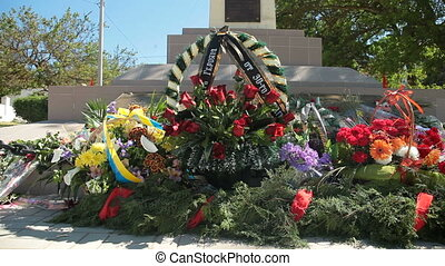 Remembrance wreaths and flowers on WW II war memorial