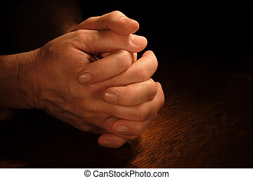 Petition - A mans hands folded in prayer with very dramatic...