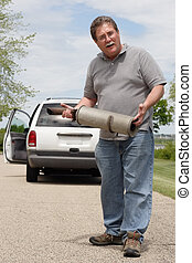 Car Trouble Series 3 - A man holds the muffler that just...