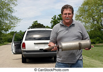 Car Trouble Series 4 - A man holds the muffler that just...