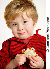 Boy eating a peanut butter and jelly sandwich - A young boy...