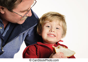 Lunchtime - Father smiling at son who is holding a peanut...