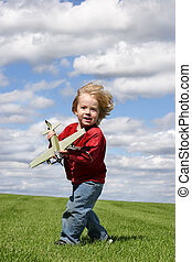 Into the wind - a young boy with a toy airplane on green...