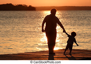 Day is Done - An adult and a child walk out on a dock as the...
