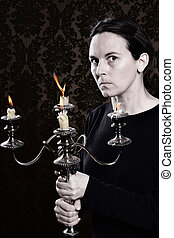 Old Hag holding a dusty and tarnished candleabra