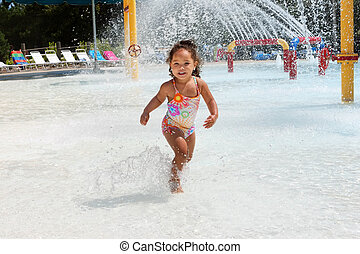 Young girl at a waterpark - Young girl dances in the water...