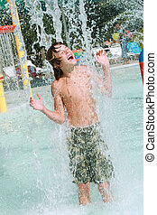 Boy playing in water at a waterpark - Teenager standing in a...