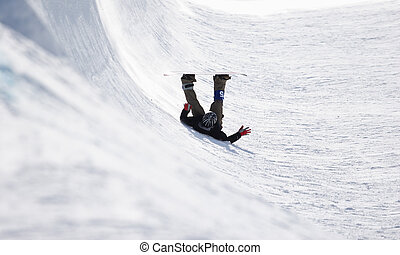 Halfpipe Competition - A snowboarder falls onto his back in...