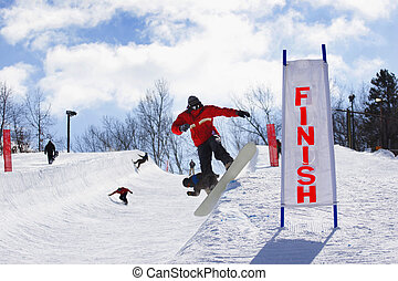Halfpipe Competition - A group of snowboarders are warming...