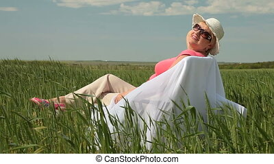 Happy senior woman relaxing on a green meadow, looking at...