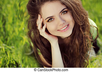 Happy smiling girl resting on green grass, outdoors portrait