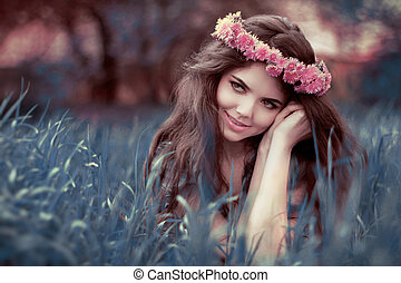 Young beautiful woman resting on grass over fairy tale park,...