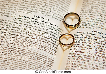 Wedding rings on a bible - The shadows of of two wedding...