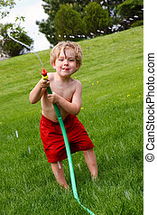 Water fight - A young boy waving a hose and spraying water