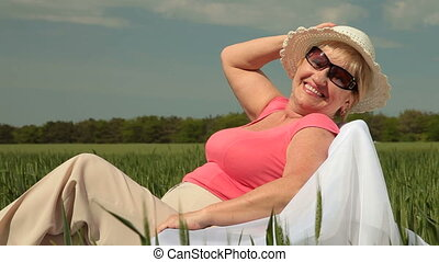 Happy Senior Woman - Happy senior woman relaxing on a green...