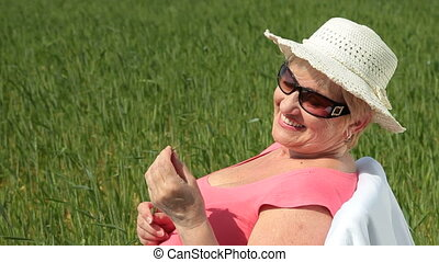 Cheerful senior woman outdoors - Cheerful senior woman in a...