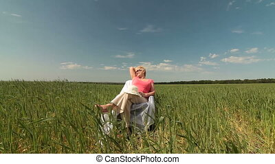 Secure Retirement - Senior woman relaxing on a green meadow