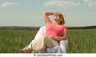 Attractive senior woman relaxing on green meadow, medium...