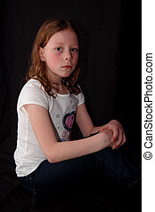 Girl sitting with hands on knees - Young girl sitting with...
