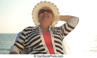 Happy senior woman enjoying vacation at the seaside, medium...