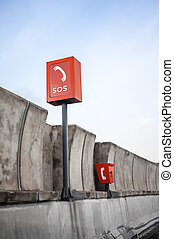 SOS sign and phone box on highway