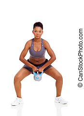 young black female doing kettle bell exercise