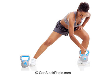 african woman exercising using kettle bell