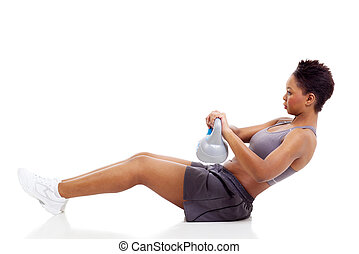 young african woman working out using kettle bell