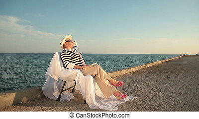 Senior woman looking to sea at sunset on the seacoast