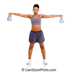 fit african woman lifting kettle bell