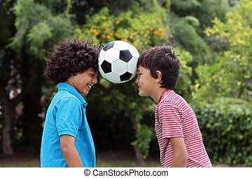 Two young boys playng with a soccer ball - Two smiling happy...