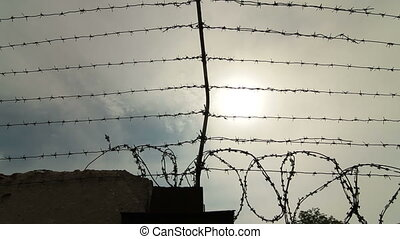 Barbed wire obstacle - Fence with barbed wire surrounding...