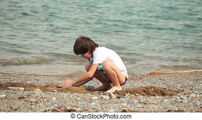 Child playing on the summer beach - Boy builds a free form...