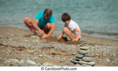Family summer beach vacation - Father and son have fun at...