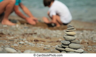 summer beach vacation - Father and son builds sandcastle on...