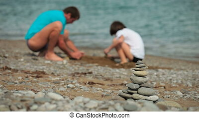Father and son builds sandcastle on the summer beach, on...