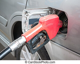 Gasoline nozzle filling up a car
