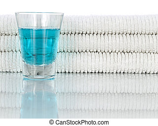 Mouthwash and towels - A glass full of mouthwash on a...