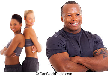 african male personal trainer and two gym members - cheerful...