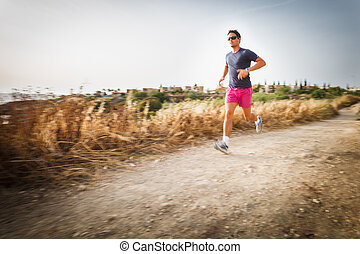 Caucasian young man running on a seacost path on a lovely...