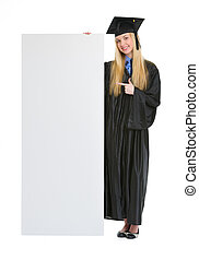 Happy young woman in graduation gown pointing on blank...
