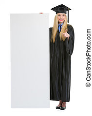 Happy young woman in graduation gown showing blank billboard...
