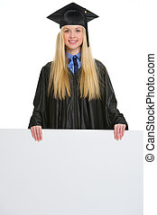 Smiling young woman in graduation gown showing blank...