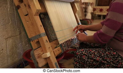 Hand-made carpet - Woman weaving a carpet