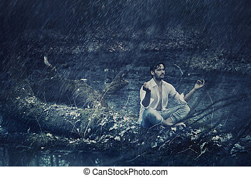 Art photo of handsome man meditating in the rain