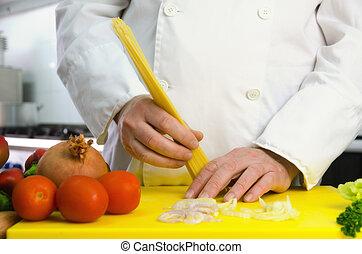 Chef hands with pasta en vegetables