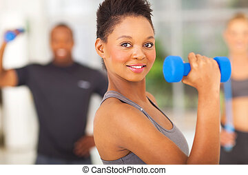 fit african woman lifting dumbbell - beautiful fit african...
