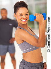 fitness afro american woman lifting dumbbell