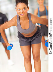 young african woman working out with dumbbells