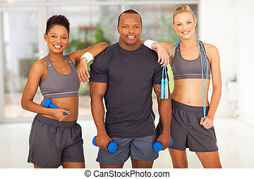 group of diversity people holding various gym equipment...
